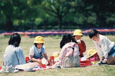 遠足で訪れた庄内緑地公園、ふかふかの芝生に座ってお弁当を広げる小学生たち