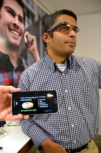 グーグルグラスを装着する米銀ウェルズ・ファーゴの担当者。手前のスマートフォン画面に映っているのは口座情報で、グーグルグラスでも確認できる=2014年11月17日、サンフランシスコ、畑中徹撮影