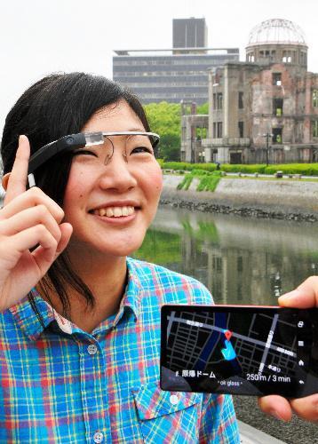 「グーグルグラス」による観光情報の表示。手前のスマートフォンに表示された地図が、利用者の目の前に表示されている=2014年5月26日、広島市中区