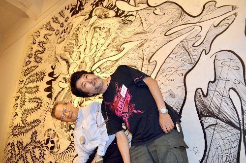 横向きに展示された作品の前でポーズをとる、作者の会田誠さん(右)と作品展を持ちかけた鎌田郁雄さん=2013年7月、香川県坂出市