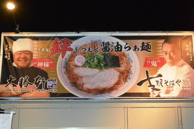 東京ラーメンショーのブースには2人が映る特製の垂れ幕も登場=22日、東京都世田谷区の駒沢オリンピック公園