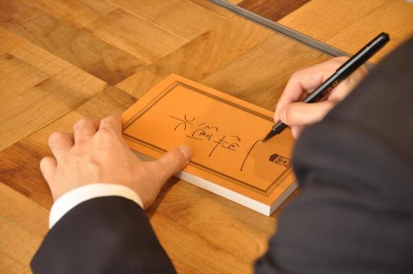 丁寧にサインを書く水野敬也さん