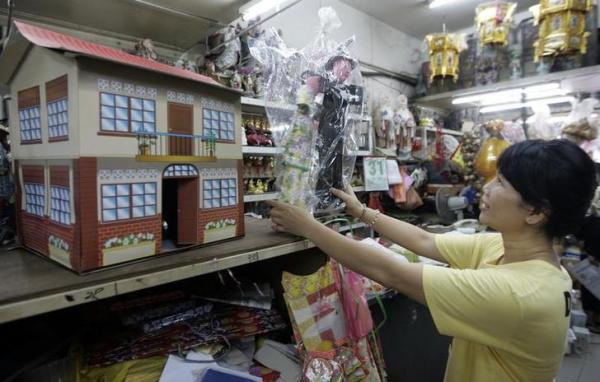 「清明節」用に売られている紙製の家や人形=2009年4月