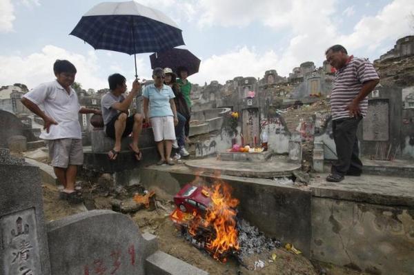 「清明節」でお供えものを燃やす家族=2011年4月