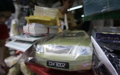 「清明節」用に売られている紙製の高級車の模型=ロイター