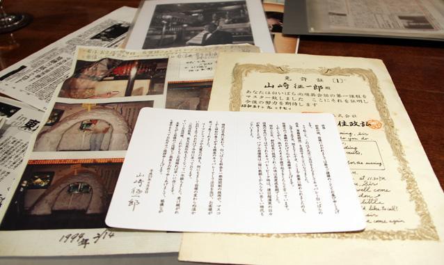 山崎さんが大切に保管している、「白いばら」の資料。アイディアマンだった先代の大住政弘社長が、海外からのお客様への対応のために考えた「白いばら必須英会話」の免許証や、お店の前にかまくらを作ったときの写真、山崎さんの引退時の挨拶状など。