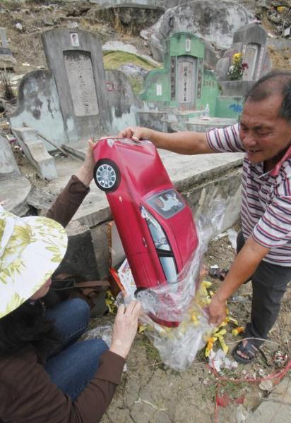 「清明節」で紙製の車をお供えする家族=2011年4月