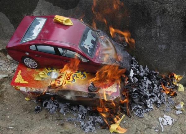 「清明節」で燃やされるお供えものの車=2011年4月