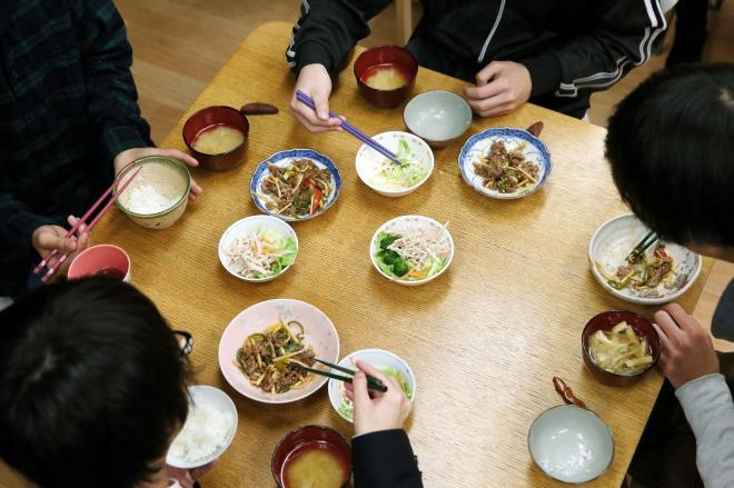 支援が必要な子どもに無料で食事を提供している団体の食堂で、晩ご飯を食べる子どもたち