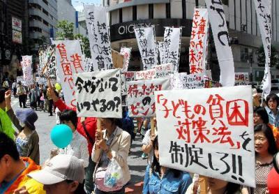 「子どもの貧困対策法」制定を求め、東京・渋谷の繁華街をデモ行進する人たち=2013年5月