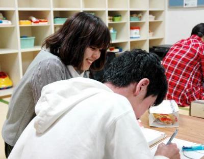勉強する子どもに付き添うボランティアの女子学生