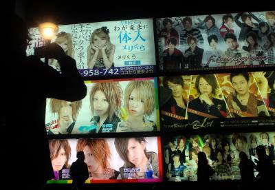 巨大な広告の前を人々が通り過ぎていく。男性がカメラを構えていた=2014年1月、新宿区歌舞伎町、吉本美奈子撮影