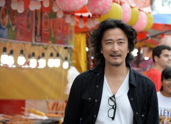 那覇市のお祭り会場で新作映画「ラスト・ナイツ」の宣伝のため名刺を配る紀里谷和明=迫和義撮影