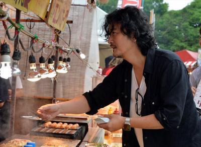 那覇市のお祭り会場で名刺を配る紀里谷和明=迫和義撮影