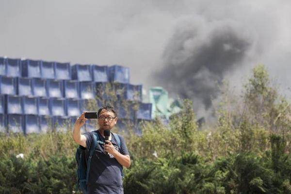 中国・天津市で起きた爆発事故をレポートする男性=2015年8月13日、ロイター