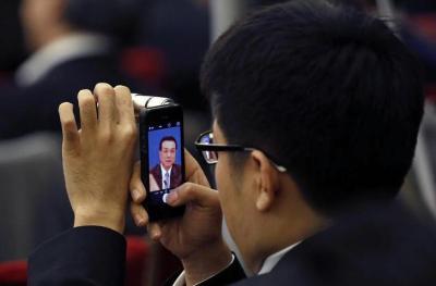 スマホで李克強首相を撮影する記者=2015年3月、ロイター