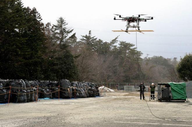 原発事故に伴う汚染廃棄物が入った袋(左)が積まれた敷地でデモ飛行する大型ドローン=2015年2月20日、福島県南相馬市、関口聡撮影