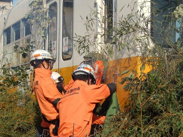運転室のドアをエンジンカッターで破砕する消防隊員。総合事故対策訓練の様子=2015年11月20日