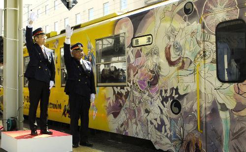 2015年、イラストが描かれたラッピング列車を見送るスクウェア・エニックスの河津秋敏エグゼクティブプロデューサー(左)