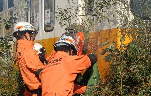 火花を散らしながらエンジンカッターで電車のドアをこじあける消防隊員=同社提供