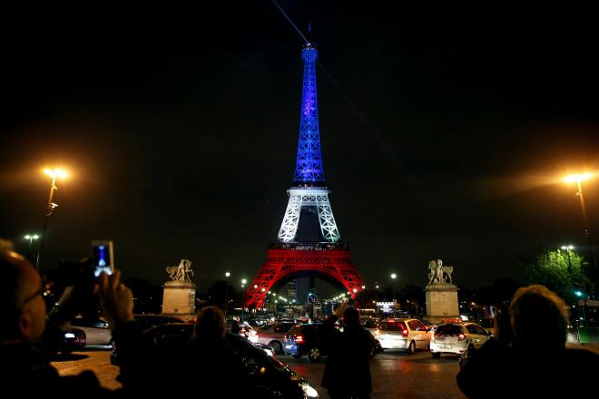 フランス国旗の色にライトアップされたエッフェル塔=16日午後、パリ、金川雄策撮影