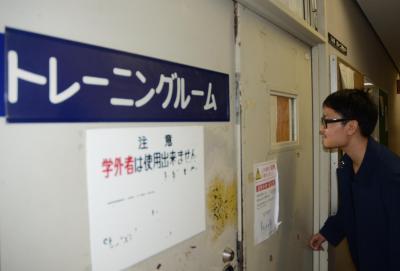 大学構内のトレーニングルームの扉についた小窓をのぞく伊藤裕佑さん