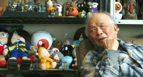 自ら創造したキャラクターのグッズに囲まれる水木しげるさん。東京・調布の仕事場で=2003年4月4日