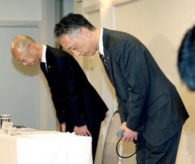 会見で頭を下げる日本マクドナルドホールディングスの青木岳彦上席執行役員(右)ら=2015年1月7日