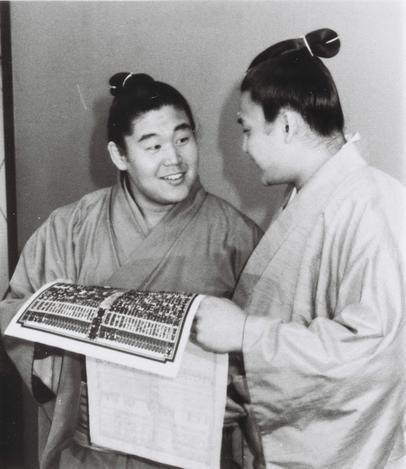 【1990年2月26日】兄弟ともに十両となった、大相撲春場所の新番付表を見て喜ぶ若花田(新十両=左)、貴花田兄弟