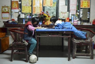 サッカーボールを置きながら宿題をする学生。壁には「賞状」がいっぱいだ。