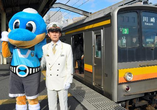 南武線・武蔵中原駅で電車の前に立つ佐藤嗣倫駅長と川崎フロンターレのマスコット「ふろん太」