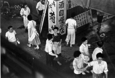 飛田本通りの商店街に進出して強引に通行人の袖を引くポンビキ=大阪市西成区飛田本通り商店街、1957年7月