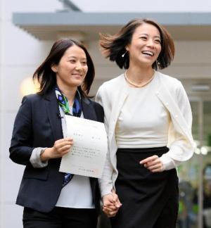 今年、渋谷区が始めた同姓パートナーへの「パートナーシップ証明書」を手に、渋谷区役所の庁舎から出てきた増原裕子さん(左)と東小雪さん=2015年11月5日