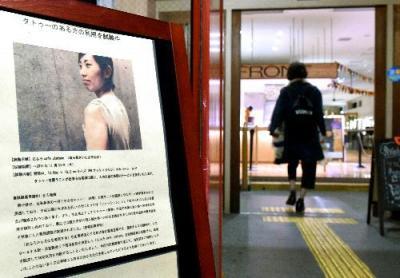 さいたま市の温浴施設の入り口には、タトゥーを隠すためのシールの試験運用を知らせる看板が立てられた=さいたま市北区、白井伸洋撮影、2015年10月19日