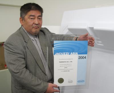 ジャクージ社から販売代理店と認定された証明を手にするタケシタの上川智之・東京支店長