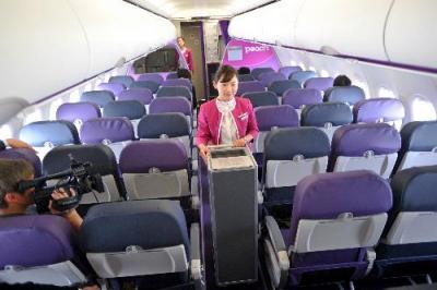 ピーチ・アビエーションの関空―福岡便のフライト訓練で、機内サービスをする客室乗務員=2012年2月28日
