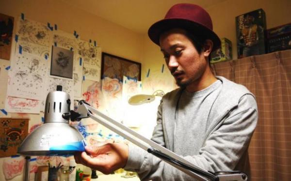 衛生のため、ライトをテープで覆う様子を再現する増田さん。彫り師として異例の法廷闘争を決意した。衛生面での懸念に「針使い捨て、滅菌器も設置」。恋人の名前は基本的に断るという=2015年12月、大阪・吹田