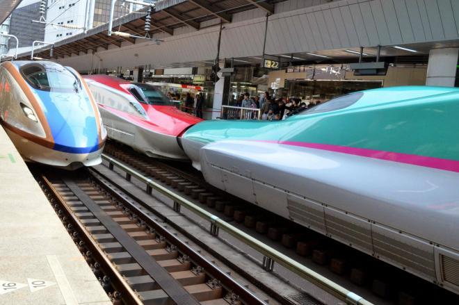 東京駅に連結して停車している東北新幹線「こまち」と「はやぶさ」の横に到着する北陸新幹線(左)=2015年3月14日