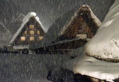 雪が降りしきるなかで照らし出された合掌造り集落=2015年1月17日
