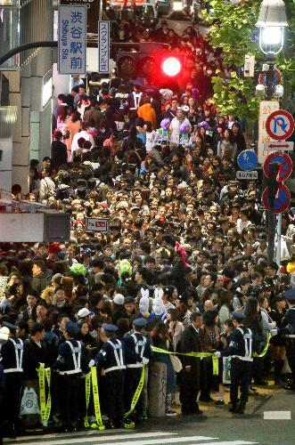 仮装した人で混雑する渋谷駅前。スクランブル交差点では大勢の警察官が交通規制していた=2015年10月31日