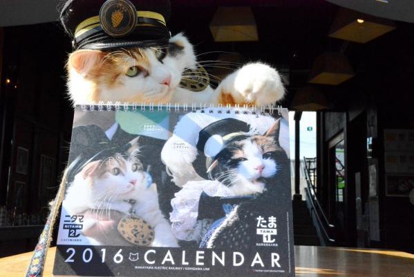 完成したカレンダーの後ろで満足げな表情の和歌山電鉄のニタマ駅長
