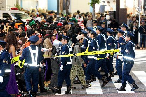 ハロウィーンの仮装をした人で混雑する交差点で、通行人を誘導する警察官=2015年10月31日