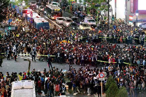 ハロウィーンの仮装をした人で混み合う渋谷駅前のスクランブル交差点。警察が規制をしていた=2015年10月31日