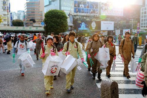 ゴミ袋を手に渋谷駅前のスクランブル交差点を渡る人たち=2015年11月1日