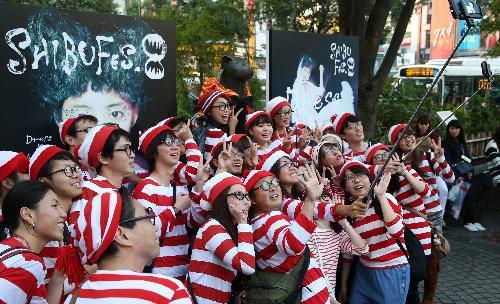 ハロウィーンに向けて盛り上がる東京・渋谷では24日、ハチ公の銅像(中央奥)も1日限定で仮装した。記念撮影をする人が絶えなかった=2015年10月24日