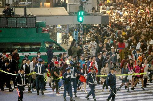 仮装した人でにぎわう渋谷駅前。スクランブル交差点では大勢の警察官が交通規制していた=2015年10月31日