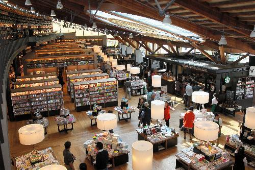 【武雄市図書館】2013年にリニューアルオープン。手前の平積みは販売ゾーンで、右奥にはスターバックスの店舗がある=佐賀県武雄市