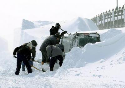 立ち往生した車の雪を掘り出す警察官=2013年3月3日、北海道中標津町