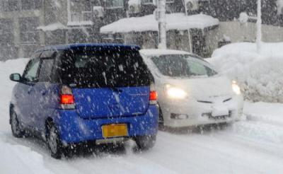 雪道を行き交う車=新潟県南魚沼市六日町、2014年12月17日