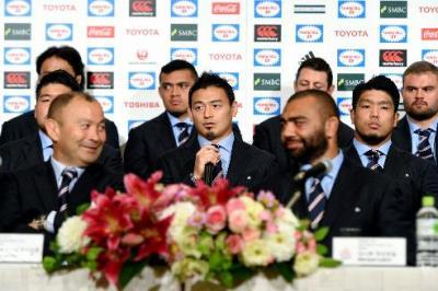 記者の質問に答える五郎丸歩選手(中央)。手前左は笑顔を浮かべるエディ・ジョーンズヘッドコーチ(当時)=2015年10月13日